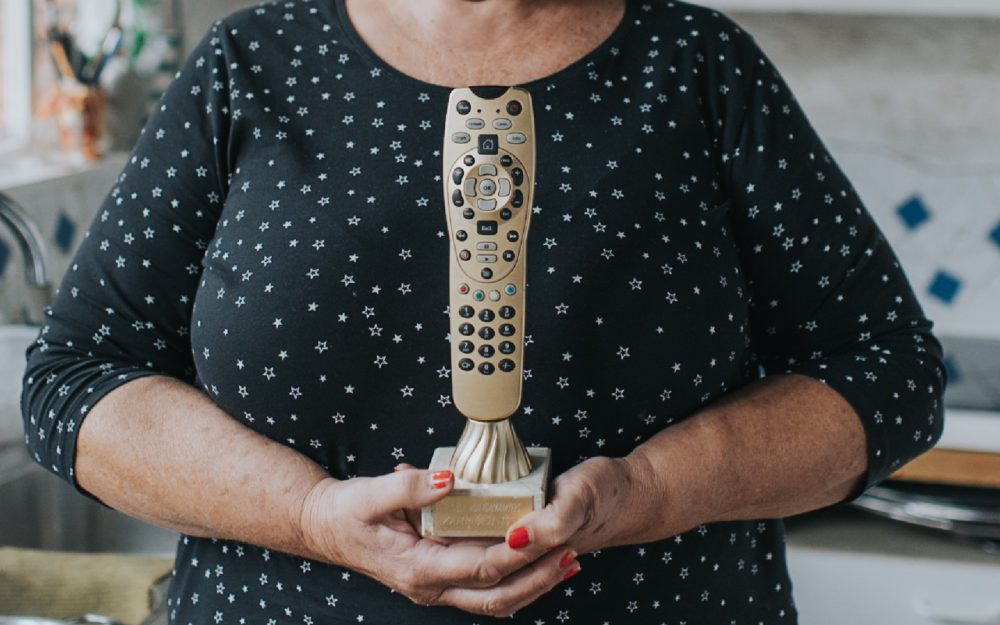 woman holding golden remote